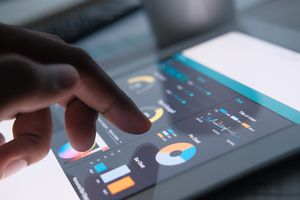 A close up of man hand with digital tablet analyzing growth charts.