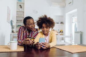 Teenage girl enjoying at home with grandmother and shopping online