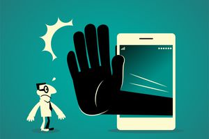 Businessman standing in front of a big smart phone (mobile phone) with a big hand making stop gesture (No!).