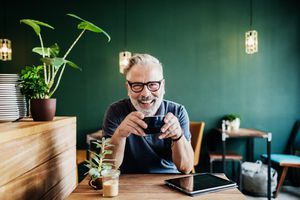 a man smiling while having a coffee in a cafe with a tablet on his desk