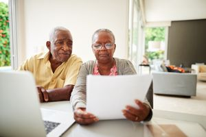 Senior couple reviews paperwork and uses a laptop