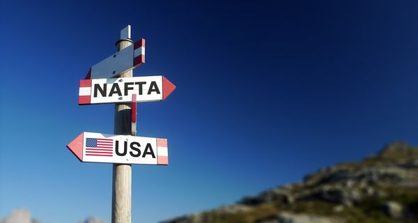 NAFTA agreement written on signpost in mountains. Negotiations concept. Withdrawal concept.