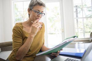 A woman reviews financial plans in folders.