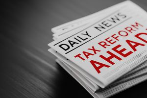Tax Reform Concept Newspaper Pile On Black Wood Surface