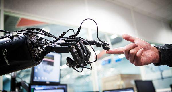 Robot touching an human hand.
