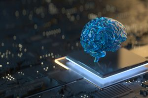 Conceptual image: A blue plastic brain atop a computer chip on a computer board, signifying artificial intelligence.