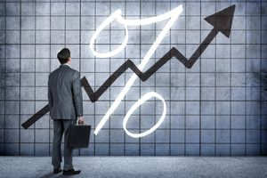 A businessman looking at a percentage with a rising arrow