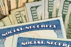 USA Social security cards laid on dollar bills.