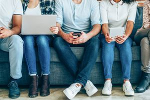 midsection image of five people sitting on a couch all holding either smartphones, a laptop, or tablet