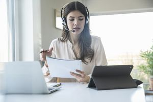 Woman working at home on laptop and wearing a headset.