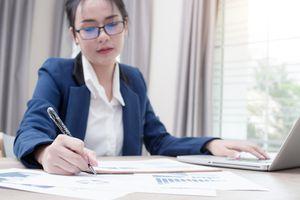 Businesswoman analyzes stock market using her laptop.