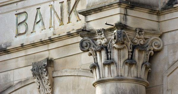 """Bank exterior showing the decorative top of a column and the word """"BANK"""" carved into the stone."""