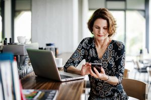 Stylish older woman at laptop with mobile phone