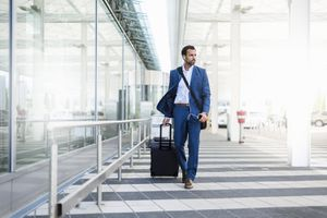 Businessperson With Trolley and Smartphone at Airport
