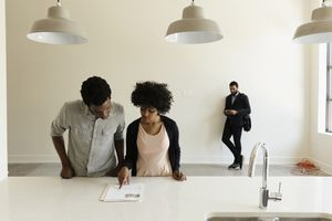 Couple reading paperwork in new house.