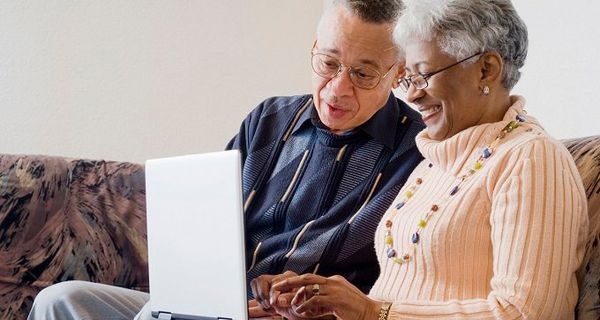 Older Black couple using a laptop