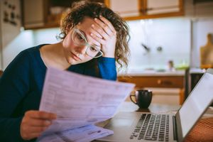 Woman sitting in kitchen, going through bills and looking worried.