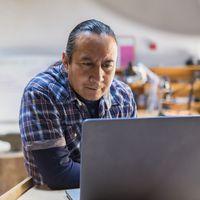 Native American man using a laptop in art studio