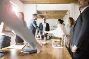 Businesspeople shaking hands during meeting in conference room