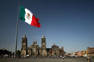Mexico City cathedral framed under the huge flag, at the Zocalo square.