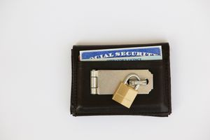 A lock on a wallet with a United States social security card and driver's license.