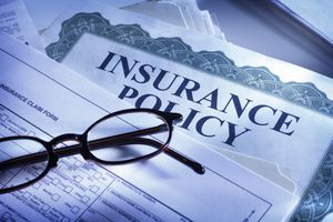 An insurance policy, claim form, and glasses on a desk
