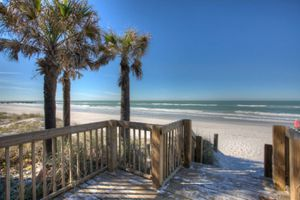Wooden deck looking out on palm trees, beach, and ocean on Anna Maria Island
