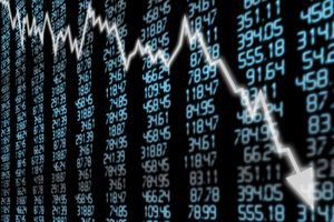 A board of stock market prices with a superimposed white arrow going down