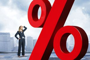 Businesswoman with hand on top of head is looking up at red percentage sign.