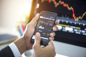 Investor analyzing stock market investments with financial dashboard on smartphone and computer screens