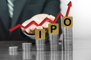 Businessman hand holding red arrow up with the letters IPO on money coin stack arranged as a graph.