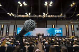 Microphone with Abstract blurred photo of conference hall with attendee background.