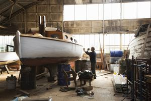Boat builder working on a boat in a shop