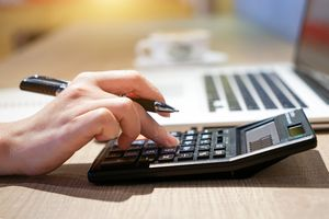 A woman hand working with calculator sitting at a desk.