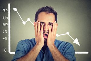 Stressed man desperate with financial market graphic going down.