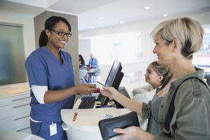 Patient paying nurse with credit card in clinic