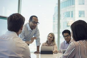 Executive MBA (EMBA) students meet with a professor.