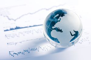 Glass globe resting on a stock chart.