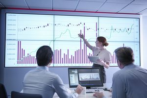 businesswoman making a presentation in front of two male colleagues in front of a screen showing graphs