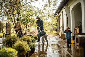 Son helping father and sweeping water from front yard on rainy day