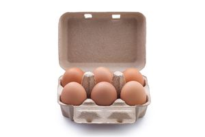 Close-Up Of Brown Eggs In Carton Over White Background