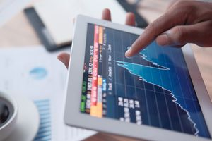 Close-up of hand pointing at stock market charts on a tablet