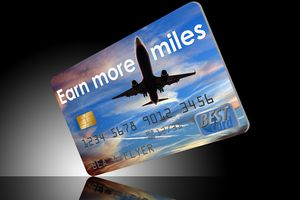 Earn more airline miles credit card on reflective dark background.