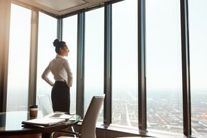 A company executive looks out the window at the city below