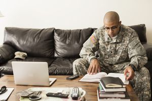Soldier in fatigues studying on sofa