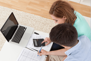 Seated couple at a low table go over finances together with a laptop and calculator.