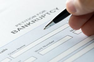 A person filling petition of bankruptcy form.