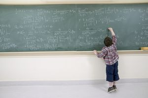 Boy Working Out Complex Equation on Blackboard