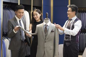 Fashion Designer Showing Customers Business Suit