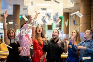 Group of Friends at the Casino Celebrating a Big Win Throwing Money to the Air